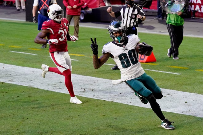 Eagles receiver Quez Watkins scores a touchdown as Cardinals safety Chris Banjo arrives too late Sunday in Arizona.