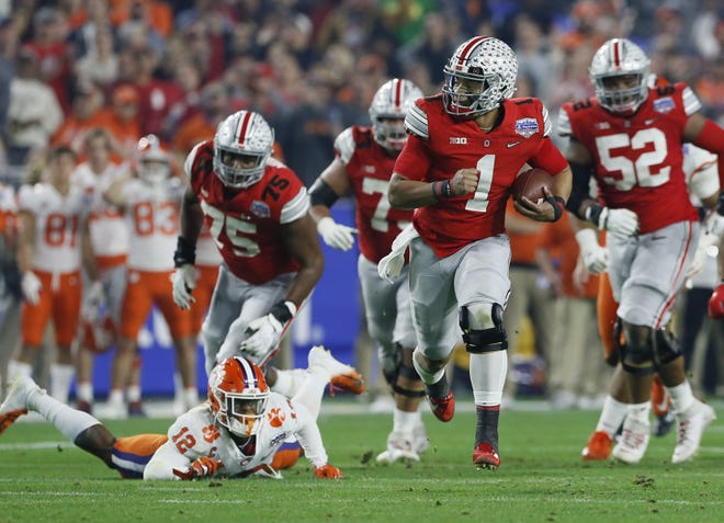 Ohio State Buckeyes quarterback Justin Fields (1) breaks away from Clemson Tigers safety K'Von Wallace (12) during the second quarter of the College Football Playoff Semifinal at the PlayStation Fiesta Bowl at State Farm Stadium in Glendale, Ariz. on Saturday, Dec. 28, 2019. [Adam Cairns/Dispatch]