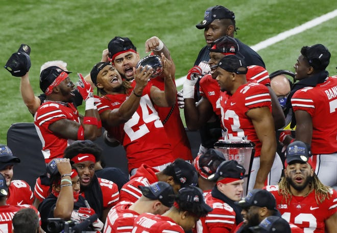Ohio State cornerback Shaun Wade holds the Big Ten championship trophy among celebrating teammates after the Buckeyes defeated Northwestern 22-10 on Saturday in Indianapolis.