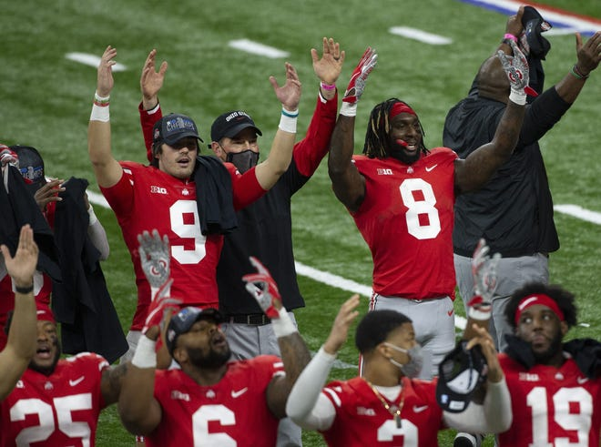 Ohio State celebrates its win over Northwestern in the Big Ten football championship game on Saturday, including quarterback Jack Miller III (9), coach Ryan Day and running back Trey Sermon (8).