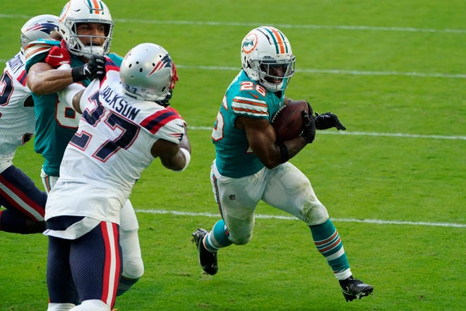 Dolphins running back Salvon Ahmed dashes for a two-point conversion against New England in Miami on Sunday.