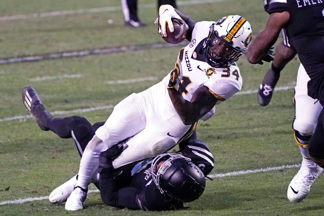 Missouri running back Larry Rountree (34) is tackled by a Mississippi State defender after a short gain during a game Saturday in Starkville, Miss.