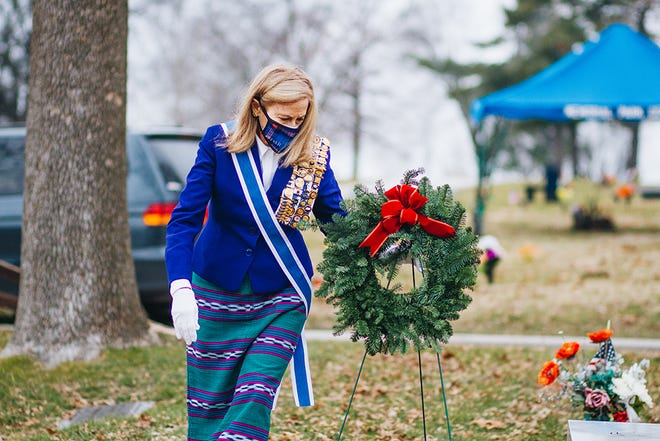 Cindy Suich places a wreath at the grave of a veteran Dec.19 in Memorial Park Cemetery in Columbia.