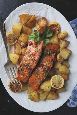 Salmon marinated in a spicy-sweet mix of brown sugar, soy sauce, ginger and chile is roasted along with potatoes for a quick and healthy dinner.