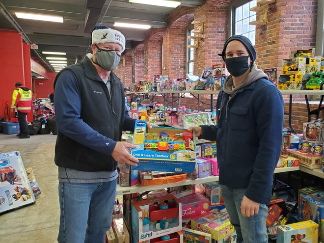 Retired Dover Fire Chief Richard Driscoll and his son, Lt. Brendan Driscoll, sort toys Sunday to distribute to families in the Dover community.