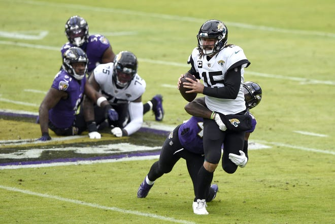 Jaguars quarterback Gardner Minshew II (15) is sacked by Baltimore Ravens linebacker Patrick Queen during the first half of Sunday's game in Baltimore.