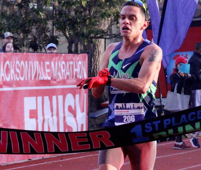 Alexander Torres crosses the finish line in record-setting time at the Ameris Bank Jacksonville Half Marathon on Sunday.