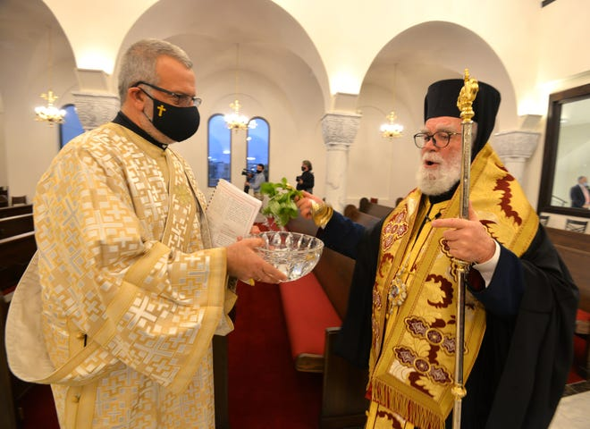 His Eminence Metropolitan Alexios of Atlanta (right) sprinkles holy water inside St. John the Divine Greek Orthodox Church, 12760 Beach Blvd., to bless the new church and welcome the faithful Saturday.