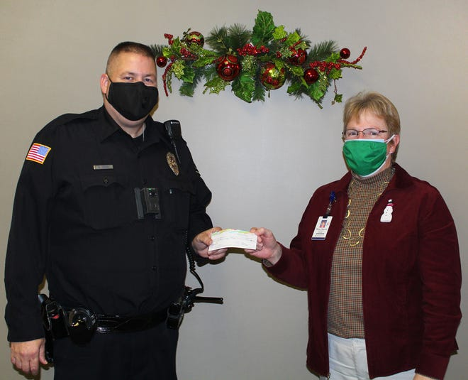 """Geneseo Police Department Detective Mike Chavez presents a check in the amount of $200 to Darcy Hepner, Hammond-Henry Hospital Foundation manager. The money will be used to benefit imaging procedures related to men's health and the funds were raised by the Police Department in November when many officers participated in """"No Shave November"""" when they did not shave for the entire month."""