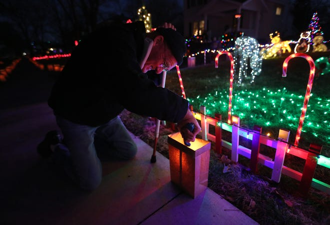 Roger Smith kneels down to light the luminaria in front of his home at 117 West 19th Ave. Saturday evening during the 37th annual Hyde Park Luminarias event in Hutchinson.