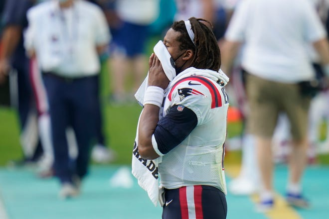 New England Patriots quarterback Cam Newton wipes his face on the sidelines during the second half of an NFL football game against the Miami Dolphins on Sunday in Miami Gardens, Fla.