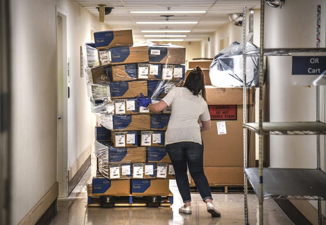 In this April 4, 2020, file photo, Bethany White, Providence Sacred Heart Medical Center supply chain manager, helps stabilize a shifting pallet of protective gowns as the third of five shipments of PPEs arrived at Sacred Heart from the state in Spokane, Wash. [Dan Pelle/The Spokesman-Review via AP]
