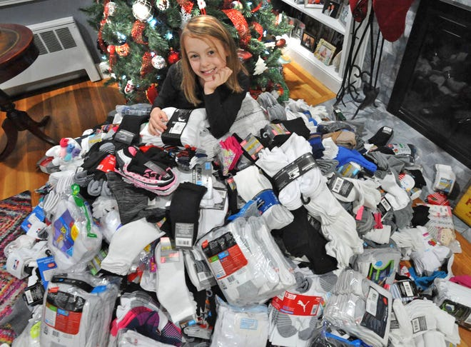 Sophia Casini of Milton, a fourth grade elementary school student, sits among the 3,175 pairs of socks in her Milton home she collected during her 6th annual sock drive for the homeless. Friday, Dec. 18, 2020. Tom Gorman/For The Patriot Ledger