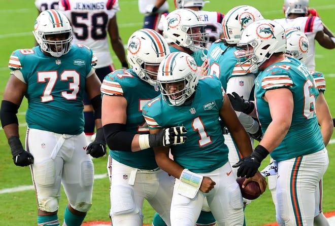 Dolphins quarterback Tua Tagovailoa (1) celebrates a fourth-quarter touchdown with his offensive linemen.