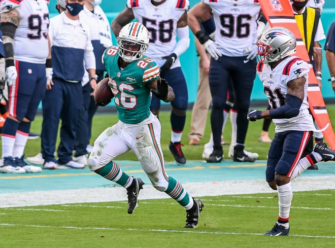 Dolphins running back Salvon Ahmed avoids the tackle of Patriots defensive back Jonathan Jones during his 31-yard run during the third quarter of Sunday's game.