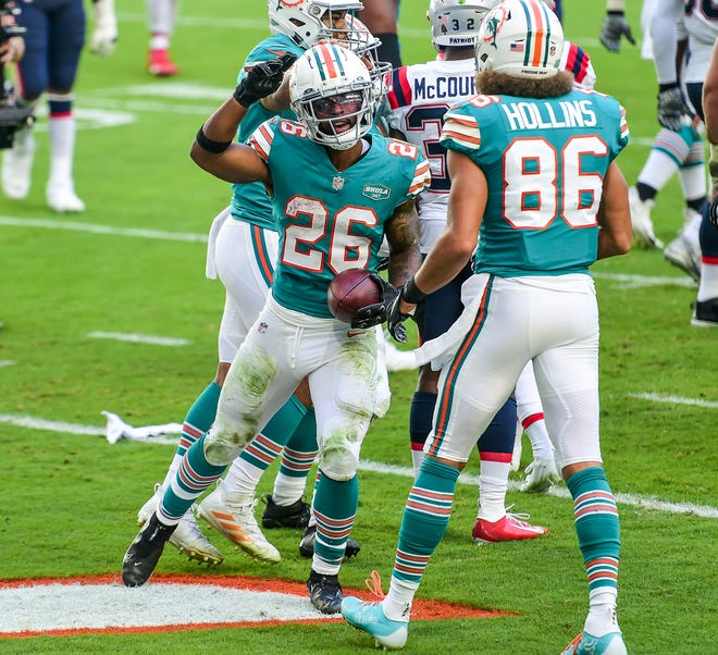Dolphins running back Salvon Ahmed celebrates his touchdown against the Patriots.