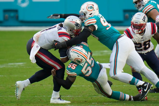 Dolphins outside linebackers Shaq Lawson (90) and Jerome Baker sack Patriots quarterback Cam Newton during the second half Sunday in Miami Gardens, Fla.