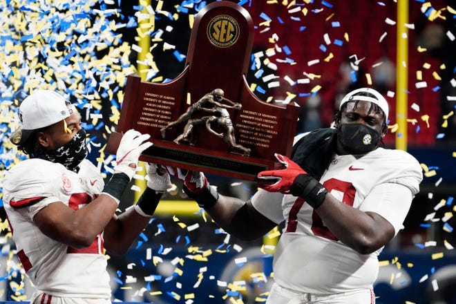 Alabama running back Najee Harris, left, and offensive lineman Alex Leatherwood celebrate their victory over Florida in the Southeastern Conference Championship Game Saturday night in Atlanta. [AP / Brynn Anderson]