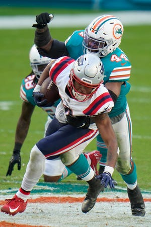 Miami Dolphins outside linebacker Elandon Roberts (44) tackles New England Patriots wide receiver Jakobi Meyers (16), during the second half of an NFL football game, Sunday, Dec. 20, 2020, in Miami Gardens, Fla. (AP File Photo/Chris O'Meara)