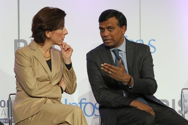 Gov. Gina Raimondo speaks with Ravi Kumar, president of Infosys, at the opening of the company's design center in Providence in 2019. Infosys is one of the companies that's inquired about a hiring extension.