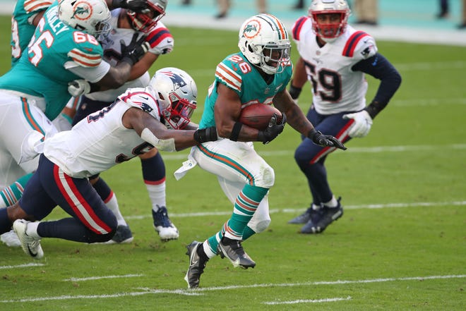 Dolphins running back Salvon Ahmed gains yardage against the Patriots' defense during the first quarter Sunday at Hard Rock Stadium in Miami Gardens, Fla.