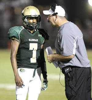 GlenOak football coach Scott Garcia talks with quarterback Brennon Tibbs.