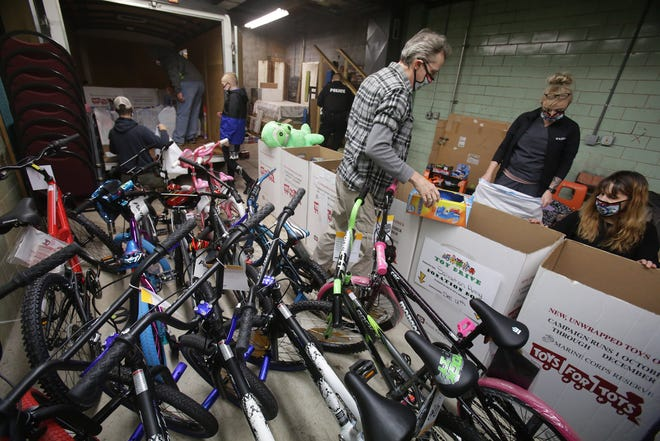 Cops-4-Kids volunteers put together bags of gifts for children at the Henderson FOP Lodge. The gifts include bikes, toys and vouchers for Walmart.