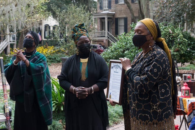 Rosalyn Rouse, left, and Patt Gunn look on as Alderwoman Bernetta Lanier reads a proclamation from the city of Savannah reconizing Jubilee Freedom Day in Calhoun Square on Sunday. Jubilee Freedom Day came with call to action this year, renaming two squares — which served as burial grounds for slaves — bearing the names of slave owners: Calhoun and Whitefield squares. [Will Peebles/Savannahnow.com]