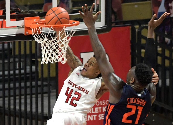 Rutgers guard Jacob Young (42) attempts to dunk the ball over Illinois center Kofi Cockburn (21) during the first half of an NCAA college basketball game Sunday, Dec. 20, 2020, in Piscataway, N.J.