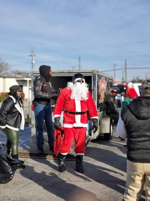 Santa (Burn City Bike Club President Jamal Williams) and his helpers prepare to deliver toys to families in Craven County. [Tina Adkins, Sun Journal]