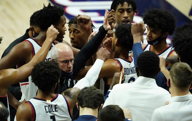 Connecticut head coach Dan Hurley, center left, talks to his team during a break in the action in the first half of an NCAA college basketball game against Creighton in Storrs, Conn., Sunday, Dec. 20, 2020. (David Butler II/Pool Photo via AP)