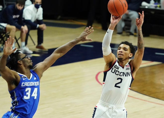 Connecticut guard James Bouknight (2) shoots against Creighton guard Denzel Mahoney (34) in the first half of an NCAA college basketball game in Storrs, Conn., Sunday, Dec. 20, 2020. (David Butler II/Pool Photo via AP)