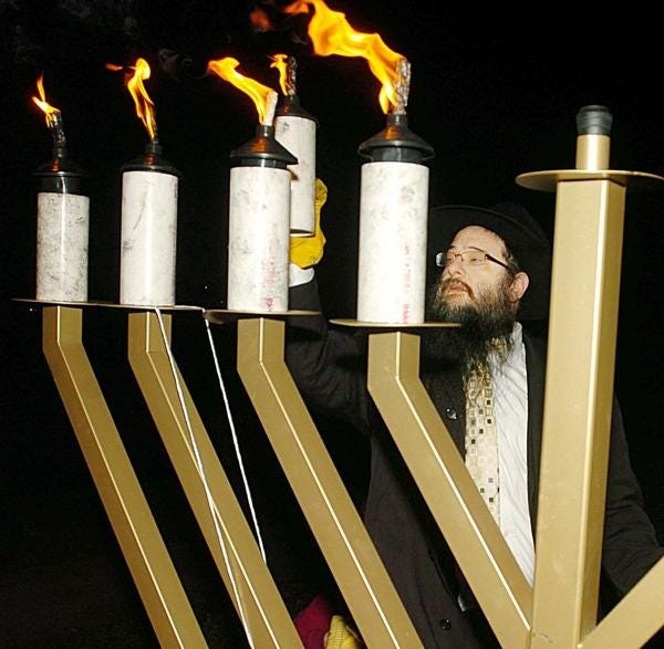 Rabbi Avrohom Sternberg, director of Chabad of Eastern Connecticut, lights a Hanukkah candle on a menorah standing on Chelsea Parade in Norwich in December 2012.