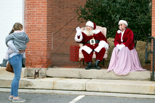 Santa and Mrs. Claus wave to a young child and mother during a Dec. 13 event at Lancaster's First Church of Christ, Unitarian.