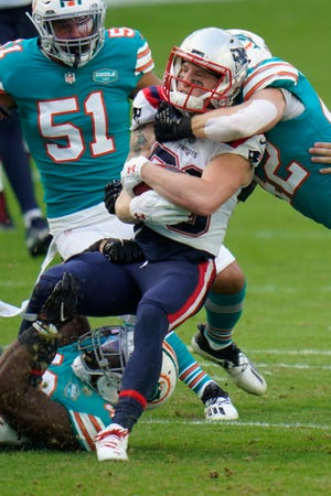 Patriots wide receiver Gunner Olszewski is tackled by Dolphins defensive back Clayton Fejedelem (42), right, and linebacker Sam Eguavoen, below, during the first half Sunday in Miami Gardens, Florida.