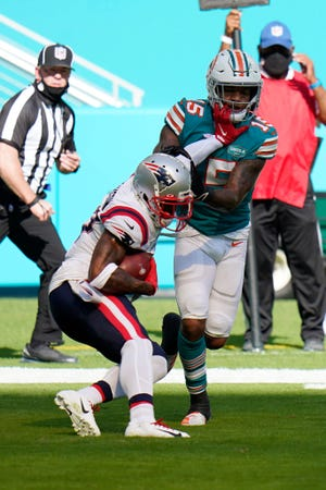 Patriots cornerback J.C. Jackson, left, intercepts a pass in the end zone intended for Dolphins running back Lynn Bowden (15) during the first half.