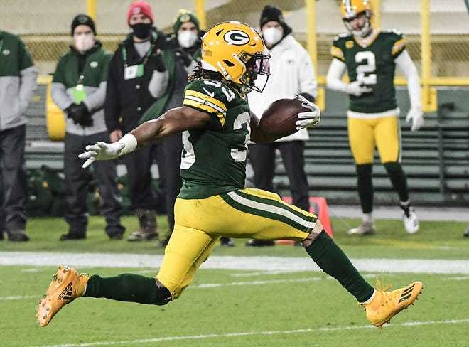 Packers running back Aaron Jones struts into the end zone for a second-quarter touchdown Saturday night against the Panthers at Lambeau Field.