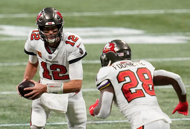 Buccaneers quarterback Tom Brady hands the ball to running back Leonard Fournette against the Falcons in the second half Sunday.