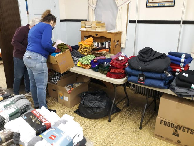 Volunteers with the Sterling American Legion Post and Project Warm-Up fill back packs for homeless veterans recently.