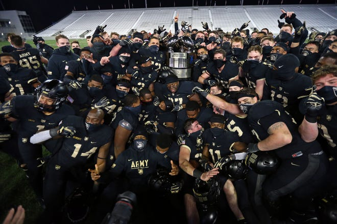 The Army Black Knights celebrate with the Commander-in-Chief's Trophy after beating the Air Force Falcons 10-7 at Michie Stadium.
