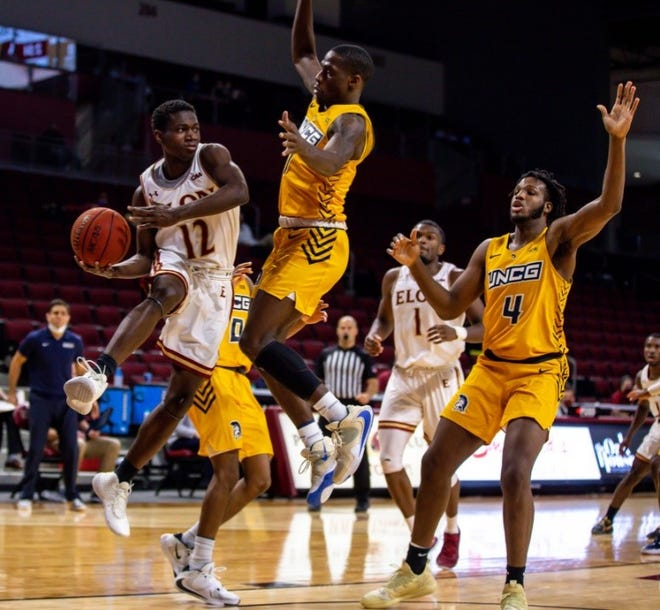 Elon's Darius Burford, left, leaps and looks for a passing angle around UNCG's Isaiah Miller and Mohammed Abdulsalam, right, on Saturday at Schar Center.