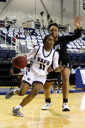 UAFS' Ashanti Eden drives the baseline around West Texas A&M University's Lauren Taylor in the fourth quarter, Saturday, Dec. 19, at the Stubblefield Center.