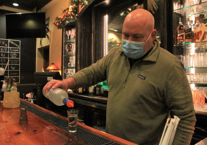 Taliano's Italian Restaurant Owner Joe Caldarera pours a shot in his restaurant hall on Friday, Dec. 18, 2020, in Fort Smith.