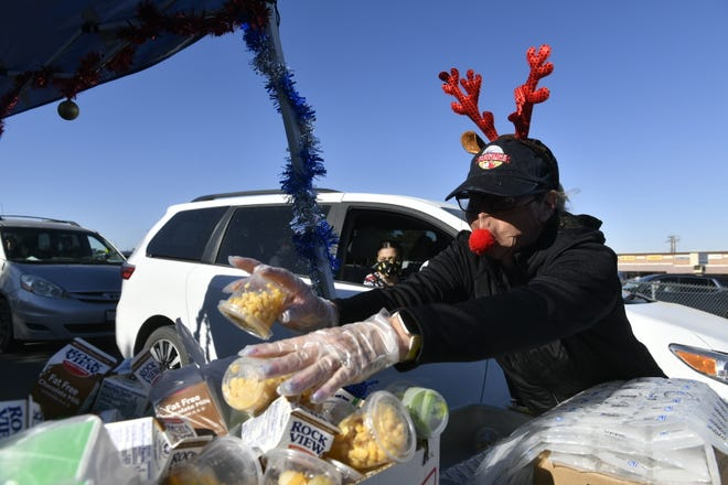 Susan Lawson prepares to load a car with enough meals to last a Snowline Joint Unified School District student through winter break during a drive-thru event in Phelan on Thursday, Dec. 17, 2020.