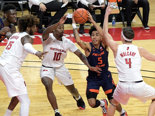 Illinois guard Andre Curbelo (5) drives to the basket as he is guarded by Rutgers guard Paul Mulcahy (4), guard Montez Mathis (10) and center Myles Johnson (15) during the first half of an NCAA college basketball game Sunday, Dec. 20, 2020, in Piscataway, N.J. (AP Photo/Bill Kostroun)