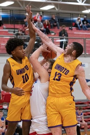 Unioto's De'Sean Branson (10) and Tayvion Galloway (13) attempt to block a shot by Zane Trace's Nalin Robinson on Dec. 19, 2020. Unioto defeated Zane Trace 50-40 to tie with Adena as leaders of the SVC.