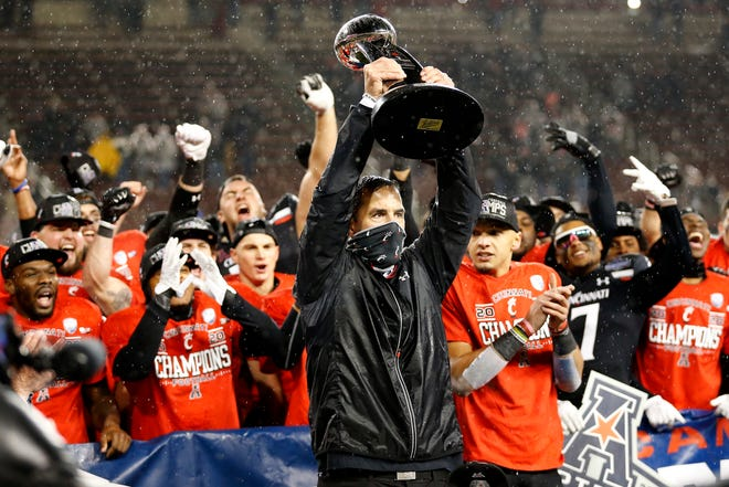 Cincinnati Bearcats head coach Luke Fickell raises the AAC Championship trophy after the fourth quarter of the NCAA American Athletic Conference Championship game between the Cincinnati Bearcats and the Tulsa Golden Hurricane at Nippert Stadium in Cincinnati on Saturday, Dec. 19, 2020. The Bearcats continued an unbeaten streak at home on their way to securing the AAC Championship title with a 27-24 win.