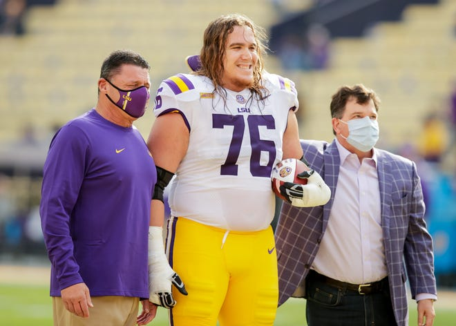Dec 19, 2020; Baton Rouge, Louisiana, USA; LSU Tigers head coach Ed Orgeron poses with LSU Tigers offensive lineman Austin Deculus (76) on Senior Day against Mississippi Rebels at Tiger Stadium. Mandatory Credit: Stephen Lew-USA TODAY Sports