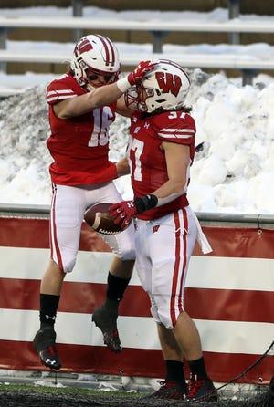 UW's Jack Dunn (16) celebrates with tailback Garrett Groshek after Groshek's touchdown run against Minnesota.