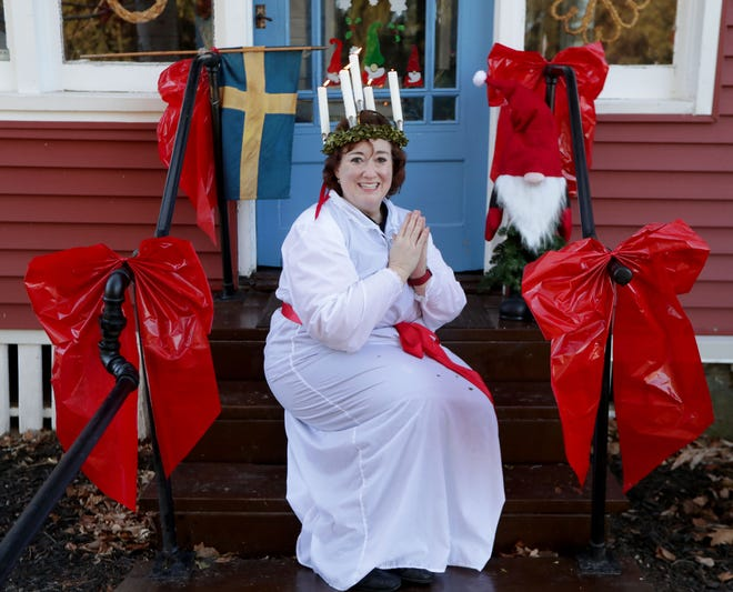 Sonia Hummel wears a St. Lucia crown of candles and a traditional St. Lucia gown in front of her home in New Berlin. Hummel has run the Milwaukee area's St. Lucia Day celebration for 25 years. She's disappointed the celebration is canceled this year, but she has found value in celebrating virtually with her family around the world.